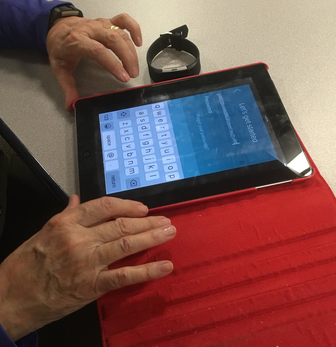 woman's hands on an older model ipad looking at fitbit login page
