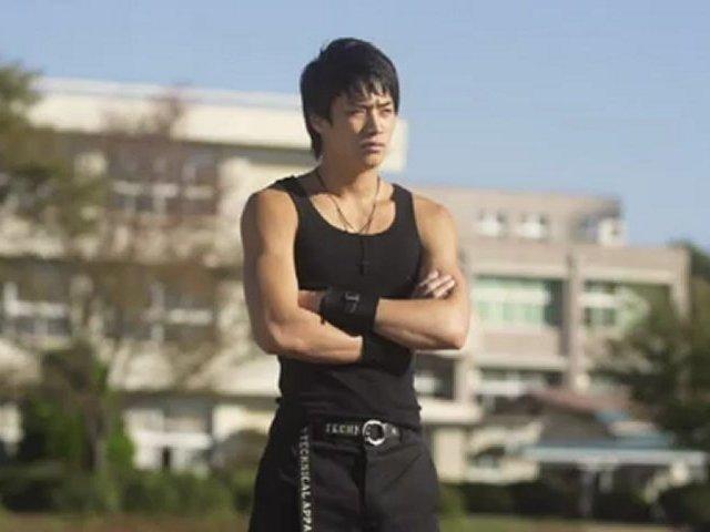 校舎を背景に遠くを見つめている鈴木伸之の高画質画像
