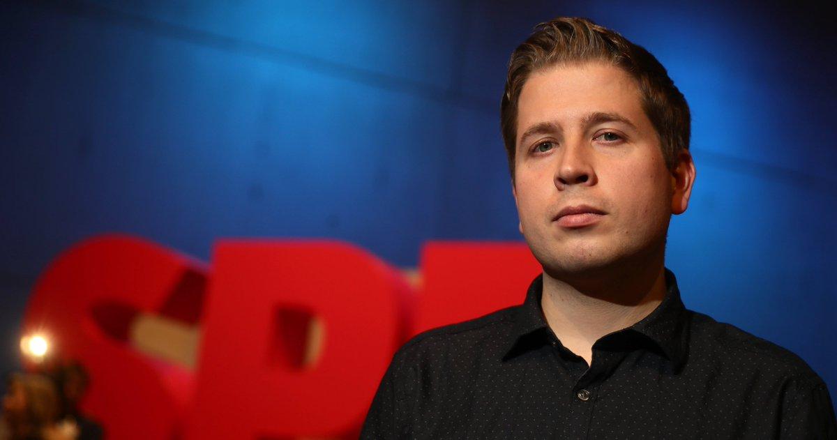 Das Foto zeigt Kevin Kühnert. Der junge Mann in schwarzem Hemd schaut streng und selbstbewusst in die Kamera.
