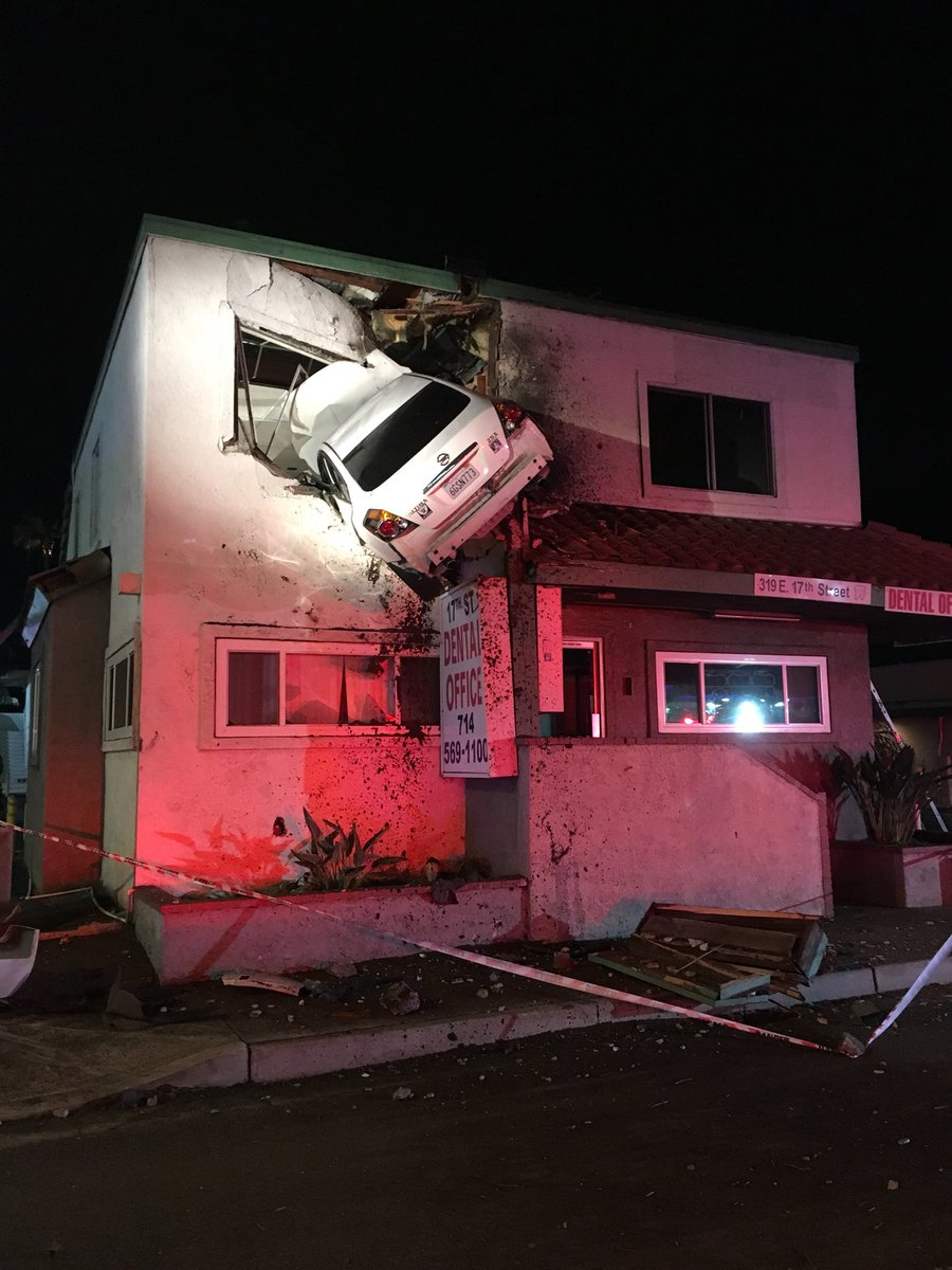 A car crashed into the second story of a building in Santa Ana, California, this morning. Officials say the vehicle hit the road's center divider and went airborne.  Photos via Orange County PIO