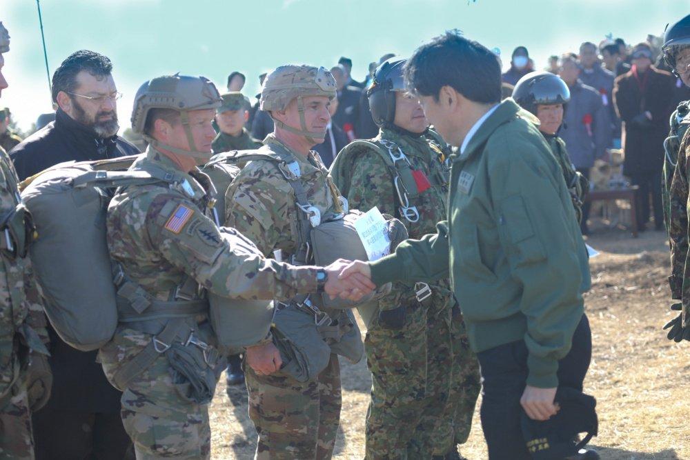 1月12日、千葉県の習志野演習場で実施された陸自第1空挺団の「降下訓練始め」に米陸軍も参加しました。写真は、米陸軍兵と握手を交わす小野寺防衛大臣。