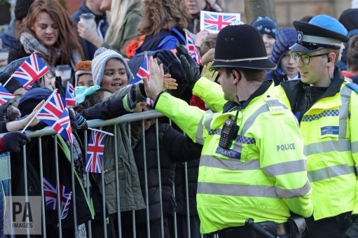 Police officers high five children as they await the arrival of #William &amp; #Kate at @CovCathedral. Pic: @aaronchown_PA<br>http://pic.twitter.com/iiUfmsxDYw