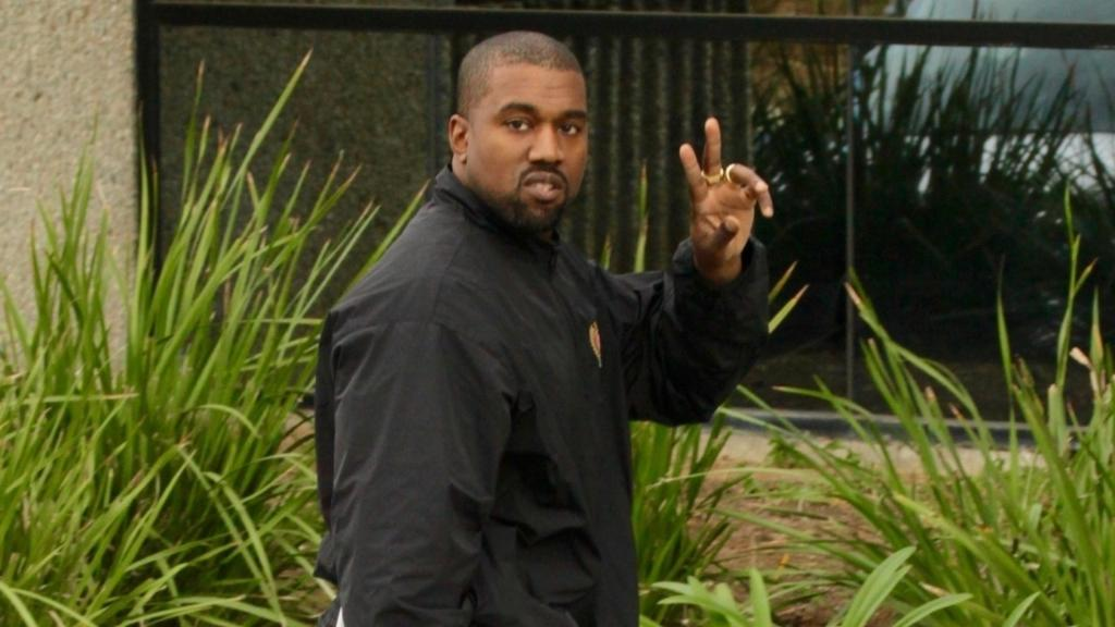 Kanye West happily heads into the office...