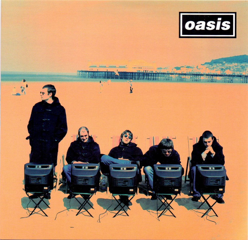"""""""This was shot on Weston Super Mare beach in Somerset. Oasis were playing Glastonbury the following day so we had to find a location within striking distance. It was red hot & the band were sat in duffle coats, much to the interest of hundreds of onlookers."""" (Brian Cannon)"""