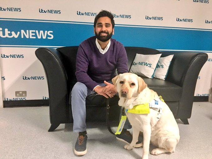 Amit is sat on a sofa with ITV news cushions on the sofa and banners with ITV news on the wall behind them. Kika is sat by his feet in harness.