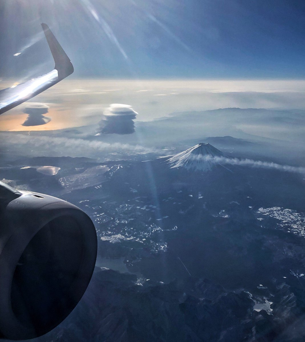 生まれて初めて飛行機から富士山見た。でも富士山より左の変な雲2つの方が気になって仕方ない。なにあれ。