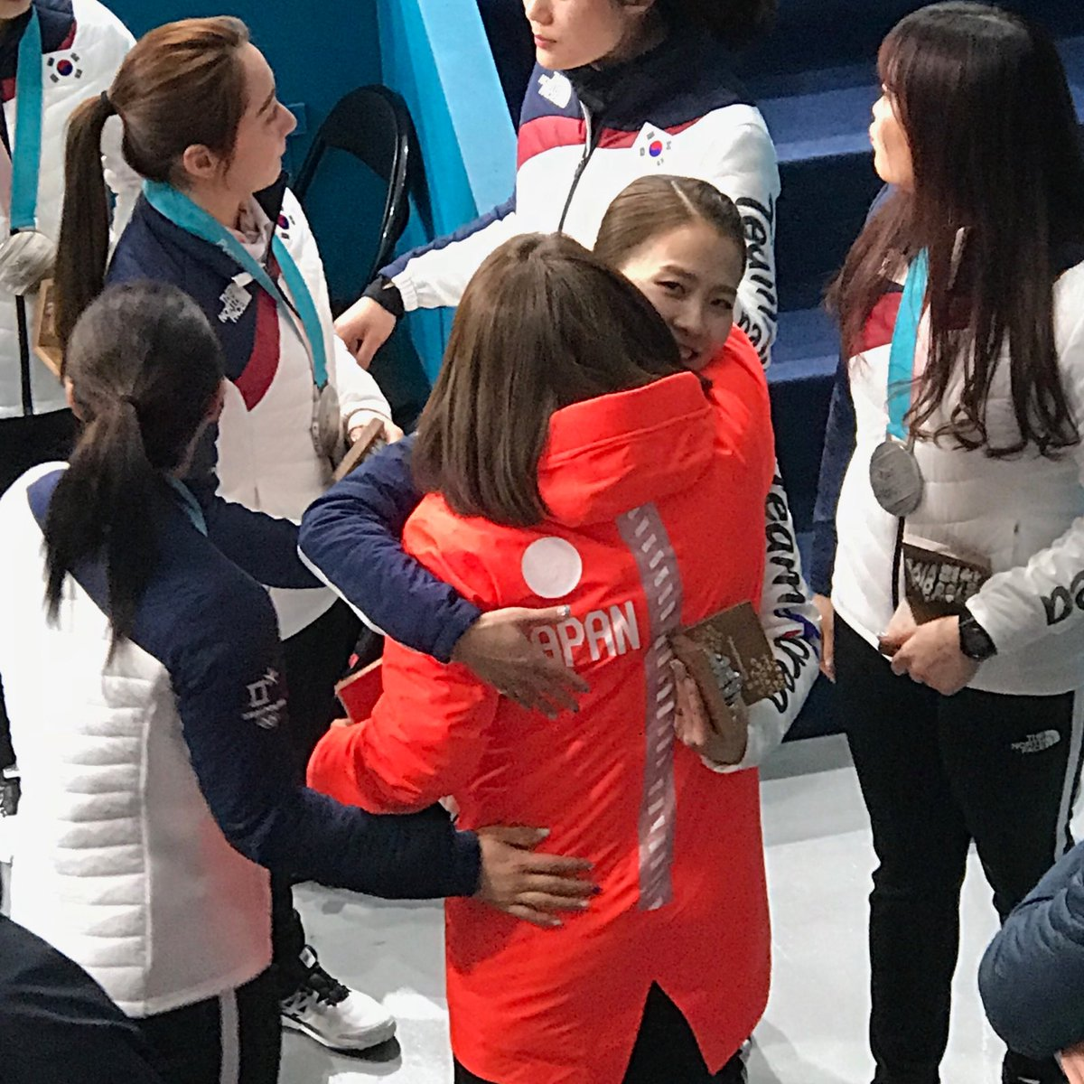 South Korean curling skip, Kim Eun-jung, aka Annie, hugs a Japanese rival after the medal ceremony
