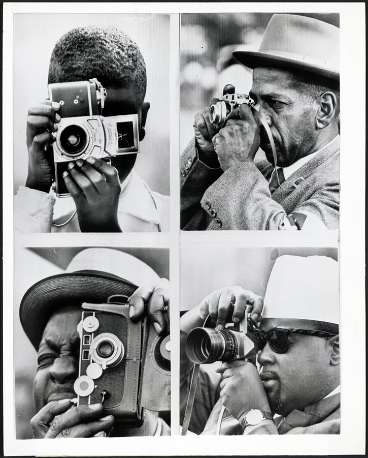 A montage of four black and white photos. Each shows a different African American man at the 1963 March on Washington, photographing the scene with his camera.