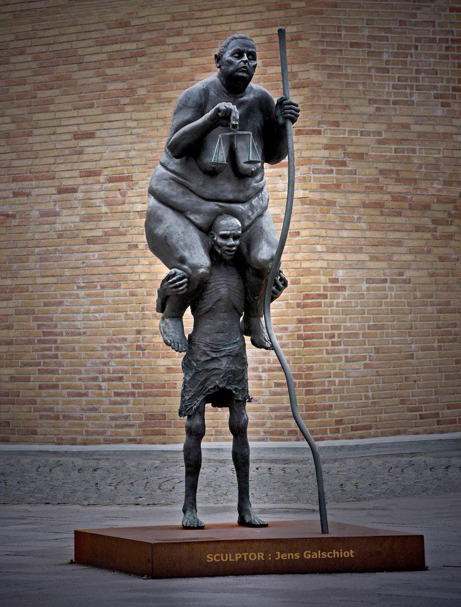 Homme pauvre portant la Justice sur ses épaules 😳  'Survival of the fattest' par Jens Galschiot