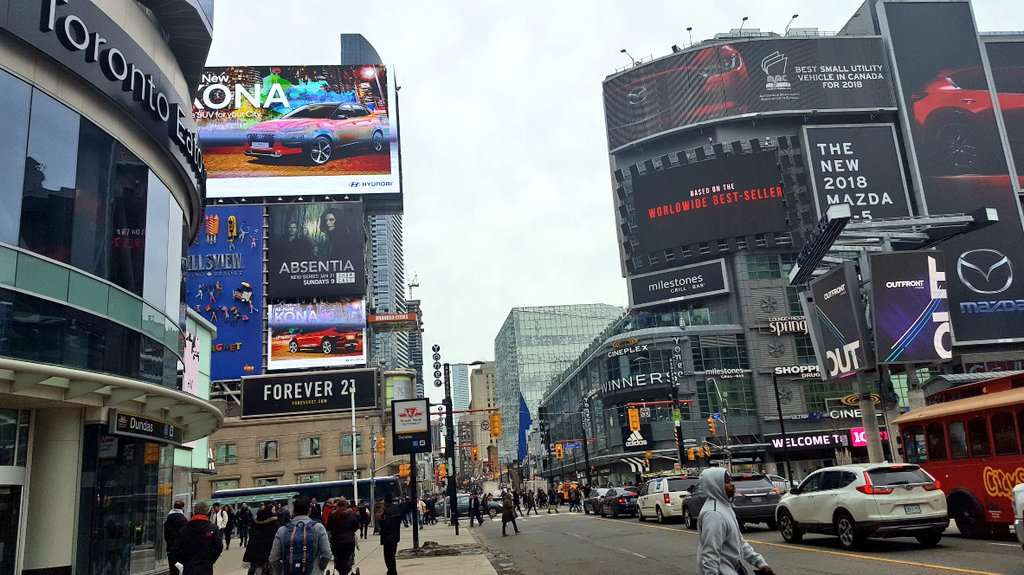 The view from down below at Dundas Square, Toronto, Canada, with neon signs and the Eaton Centre