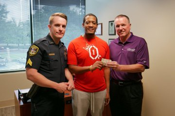 Man who returned money poses with Sgt. Parsons and Chief Grogan.