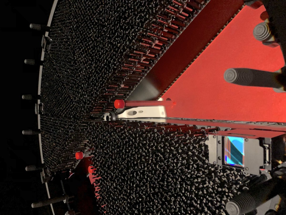 PROGRESS: Heres the DESI focal plane with 7 of the 10 petals installed. You are looking at the input end of 3,500 positioners! 📷 by Robert Besuner More info: In the foreground is one of the guiders. The red wedges are panels where the next petals will be inserted.