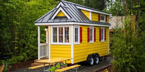 """Just one of the homes in Oregon's Mt. Hood Tiny House Village, """"Savannah"""" features yellow cedar plank siding with red shutters and white trim. So welcoming! #tinyhome #tinyhouse #tinyhousemovement #vanlife #tinyhouseonwheels #tinyhousenation"""