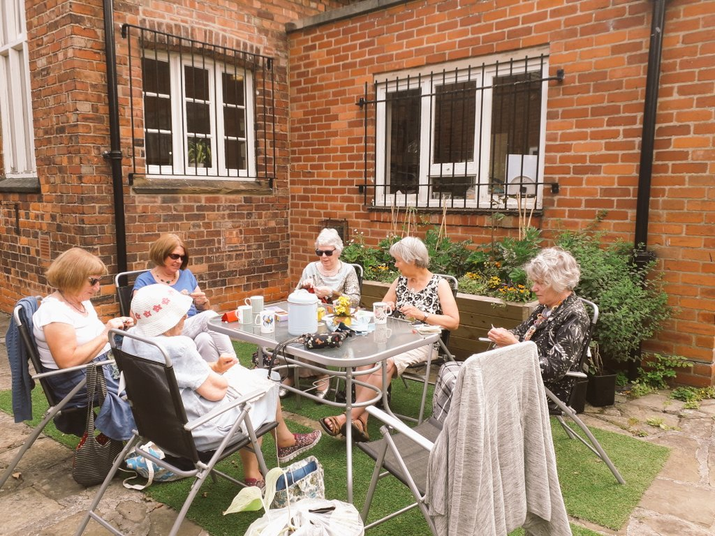 The Knit &Natter group enjoying the sunshine in the patio - spot the thriving tomato plants in the background! #community #loveyourlibrary #ExploreMore