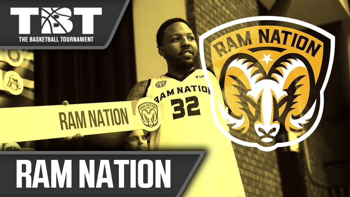 """A basketball player holds a placard that says """"Ram Nation"""""""