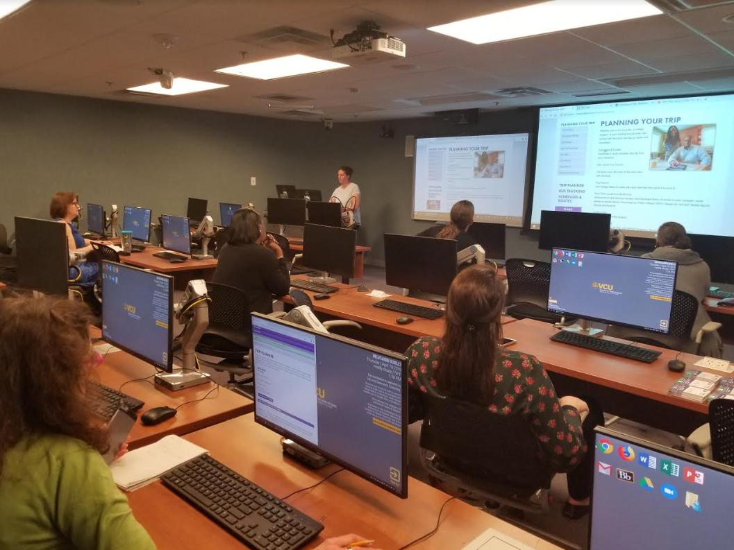 classroom of employees sitting behind computers while a GRTc travel training instructor guides them at the front of the classroom.