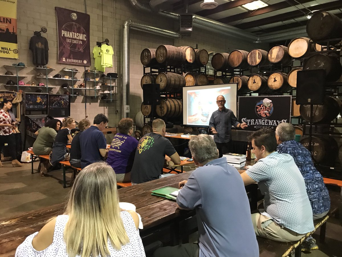 Image description: Students seated at tables in a barrel room listening to an instructor who is standing in front of a screen