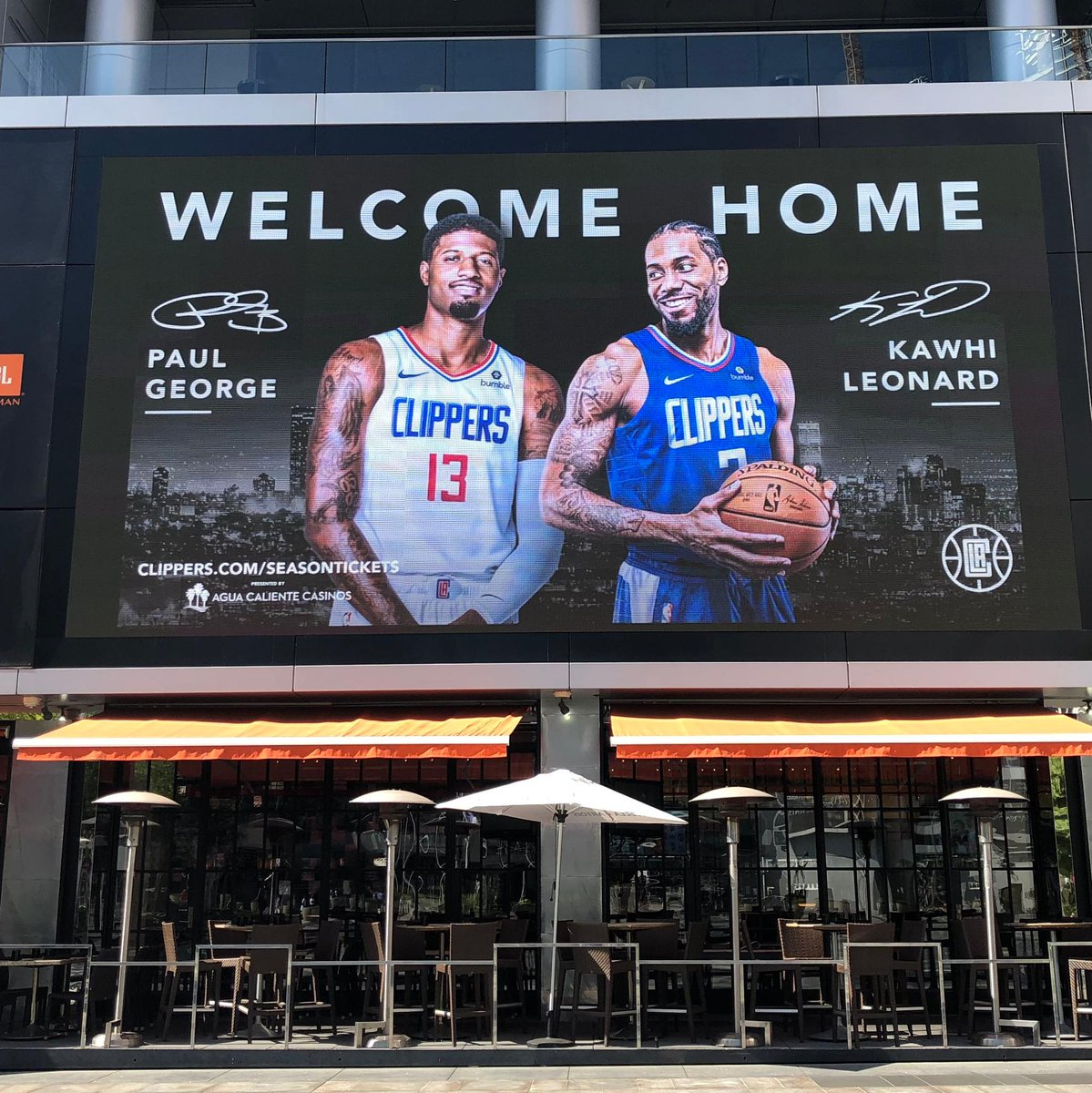 The Clippers welcome PG and Kawhi home on billboards across from Staples Center.