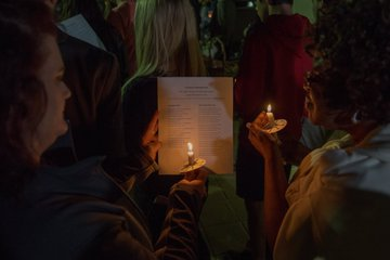 Students holding up candles to a program to read words to a hymn