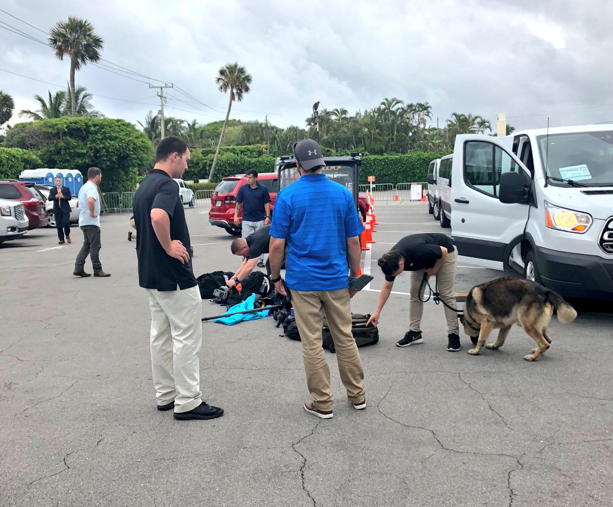 Secret Service bomb-sniffing dog helping agents with sweep of WH press pool gear at Mar-a-Lago.