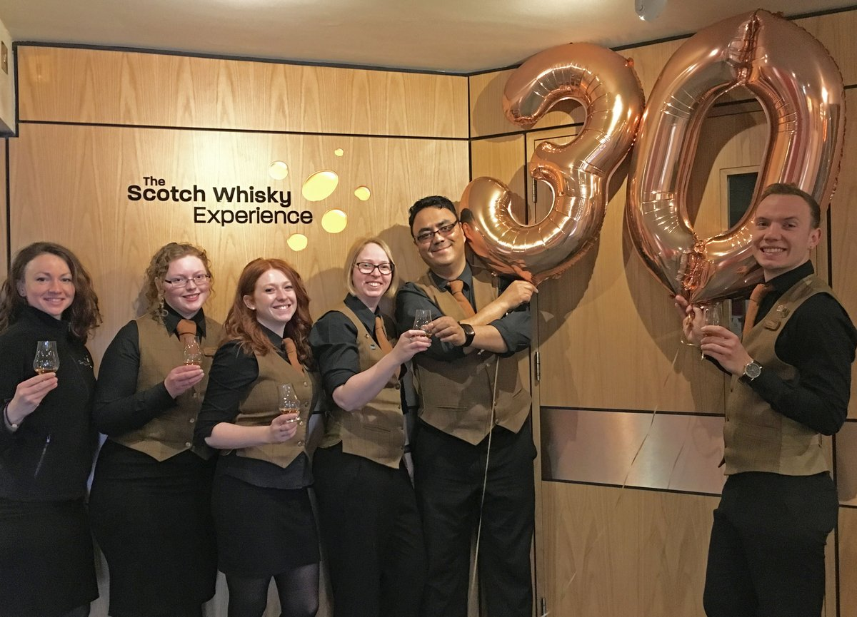 SWE staff standing with 30th birthday helium balloons