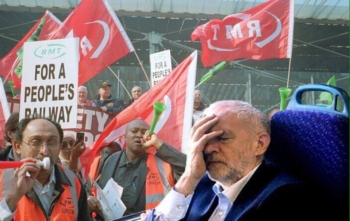 Jeremy Corbyn sits on a train with his head in his hands.