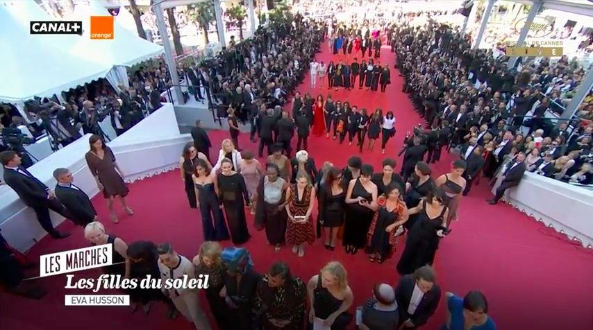 "Rows of 8-10 women, arms interlinked, are walking red carpet@ #cannes. The announcers call it ""an important, powerful image,"" noting that ""the awareness that has come since H-Day, Harvey Day, as it is called, unfort. a terrible event & the consequences nevertheless can b v impt."""
