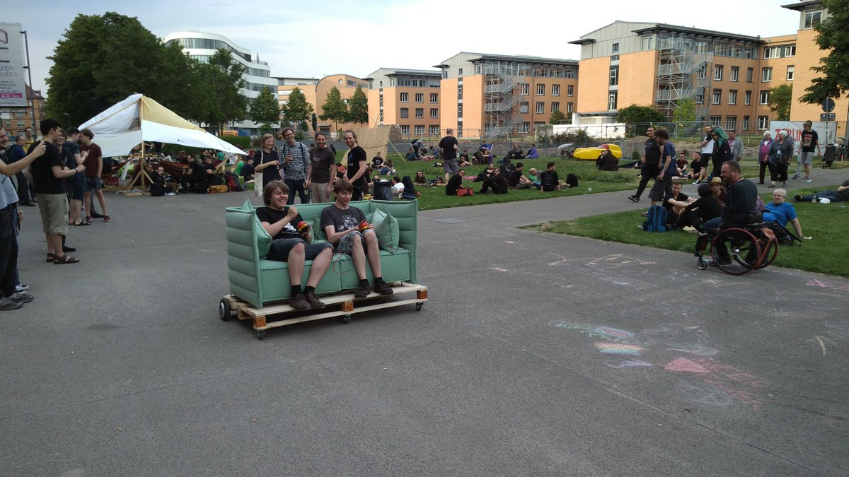 A two person motorised sofa being driven outside the ZKM.