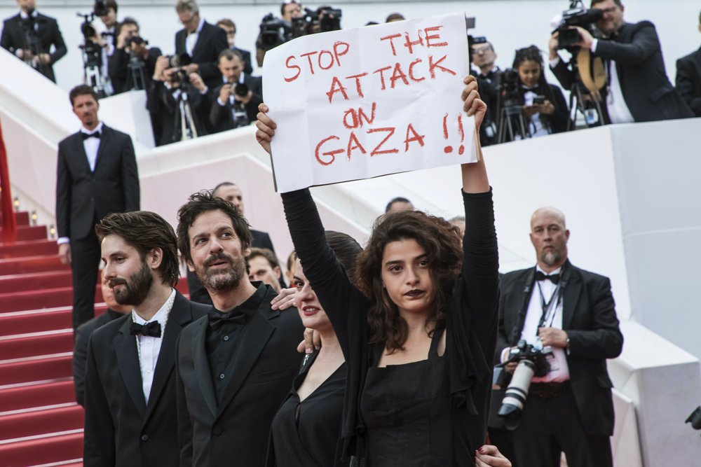 Lebanese actress Manal Issa holds a sign that reads 'Stop the Attack on Gaza' at the premiere of 'Solo: A Star Wars Story' at #Cannes2018. Israeli soldiers shot and killed 59 Palestinians in mass protests on the Gaza border on Monday. (Photo by Vianney Le Caer/Invision/AP)