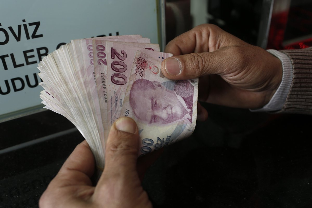 A Customer Counts Turkish Lira Banknotes At Currency Exchange In Istanbul