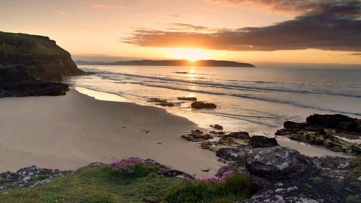 A beautiful sunset over Castlerock beach. The sun casting a warm glow over the sea.