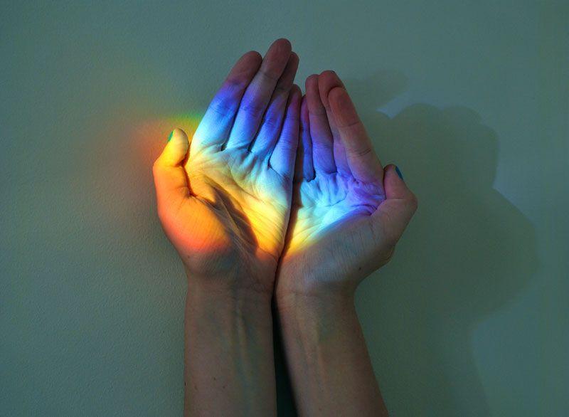 Mains qui attrapent un arc-en-ciel créé par un prisme