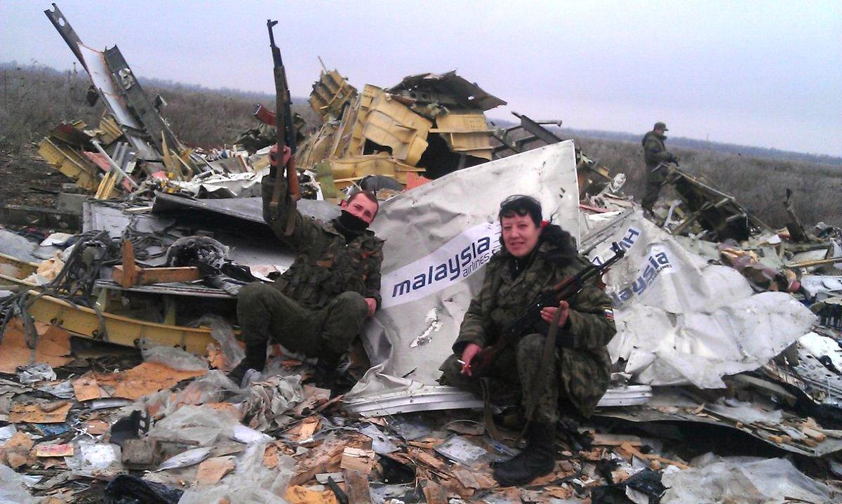 Bruņotie kaujinieki pozē uz notriektās lidmašīnas atlūzu fona