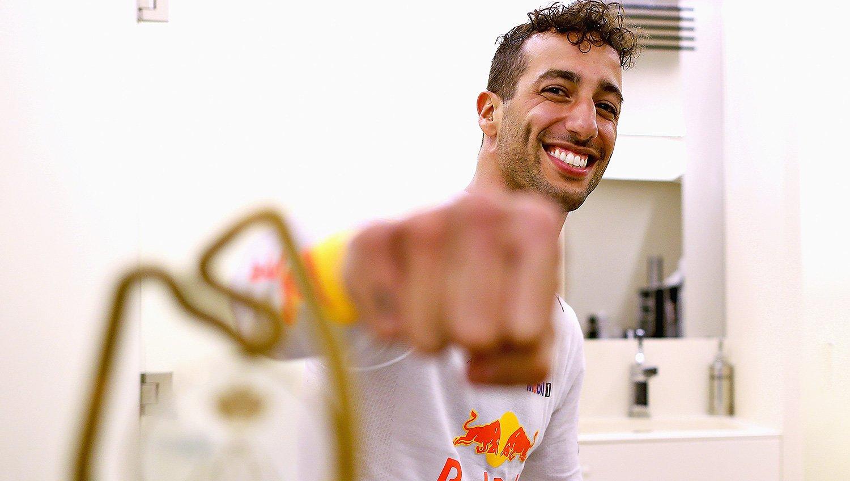 Daniel Ricciardo fist bumps the camera with the Monaco Grand Prix winners trophy.
