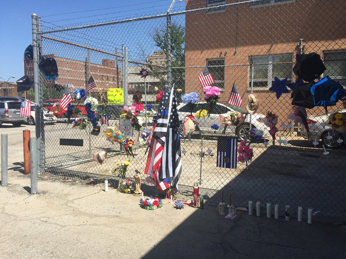 The memorial in Kansas City, Kansas, continues to grow near the spot where Wydanotte County Deputies Theresa King, 44, and Deputy Patrick Rohrer, 35, were shot and killed by an inmate Friday during a prisoner transport.