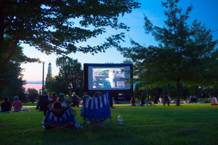 People watching a movie on the lawn outside of Hayes Hall on UB's South Campus at dusk