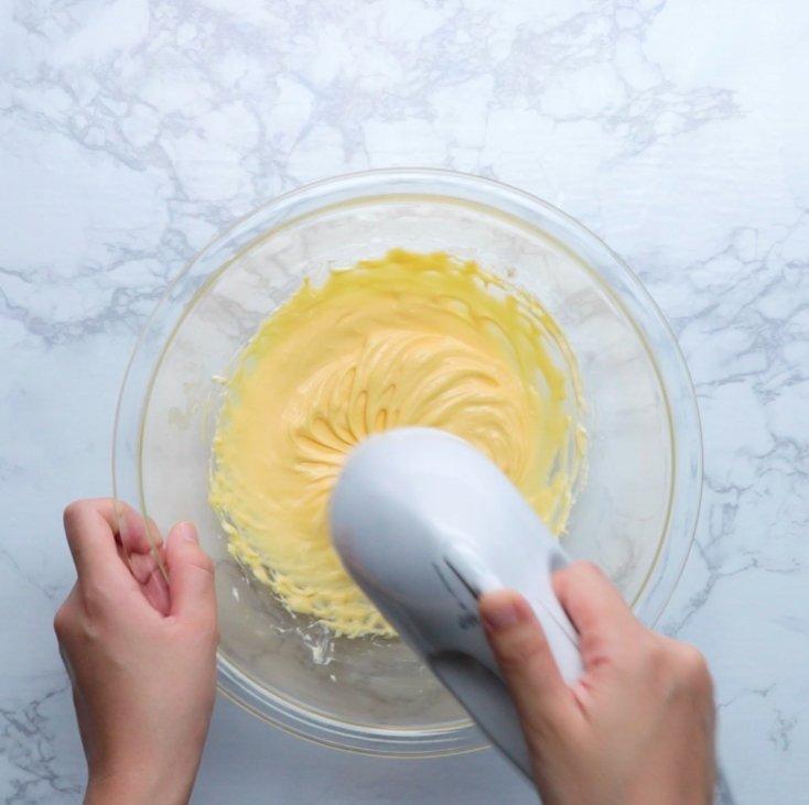 2. 別のボウルにクリームチーズと残りの砂糖を入れ、ハンドミキサーで混ぜる。なめらかになったら卵黄、生クリーム、レモン汁を加え、よく混ぜる。