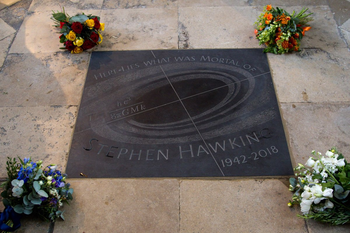 The memorial stone of Stephen Hawking surrounded by flowers laid by his family
