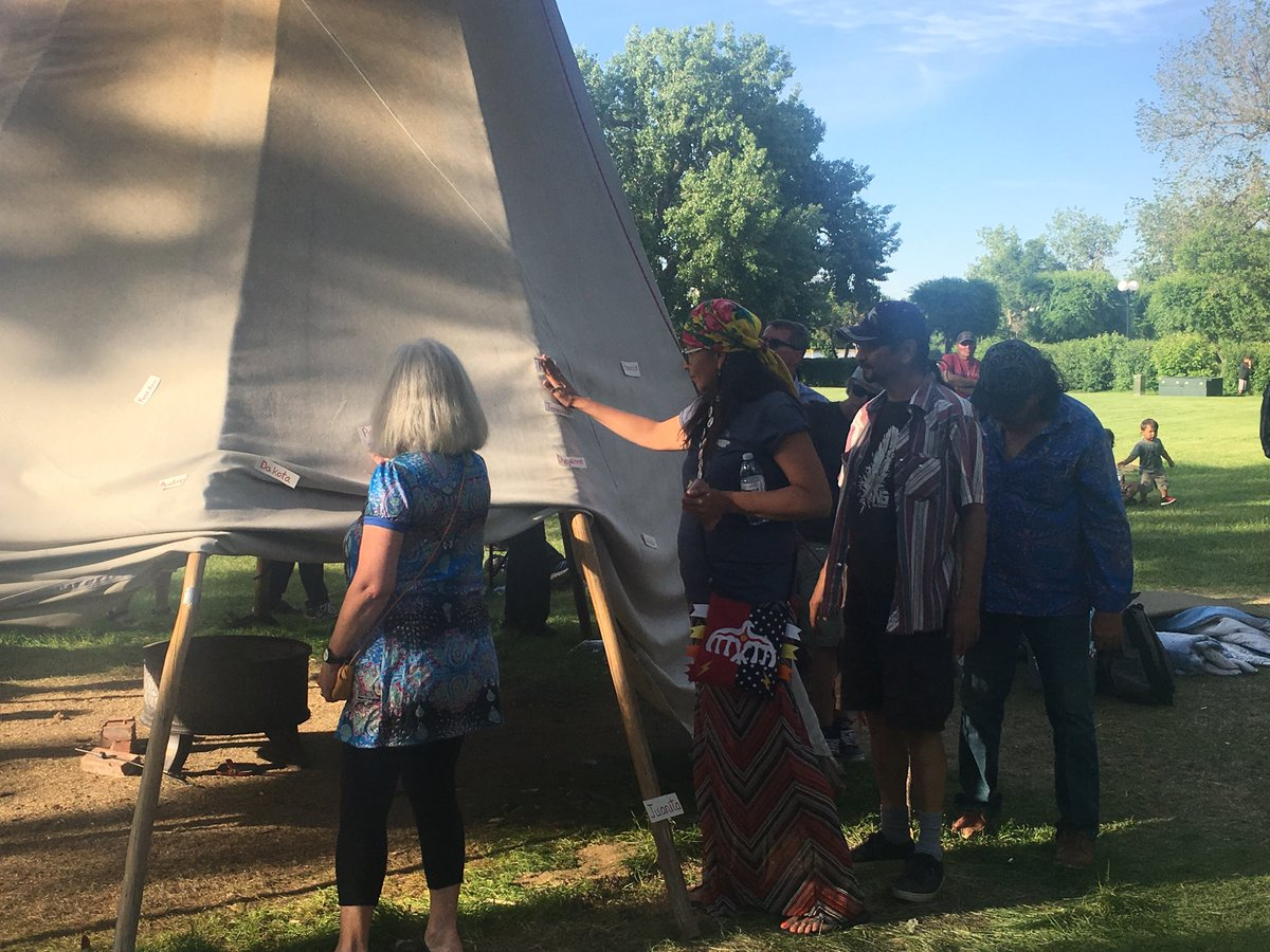 Public touch the names of murdered and missing women before tipi comes down in Wascana Park.