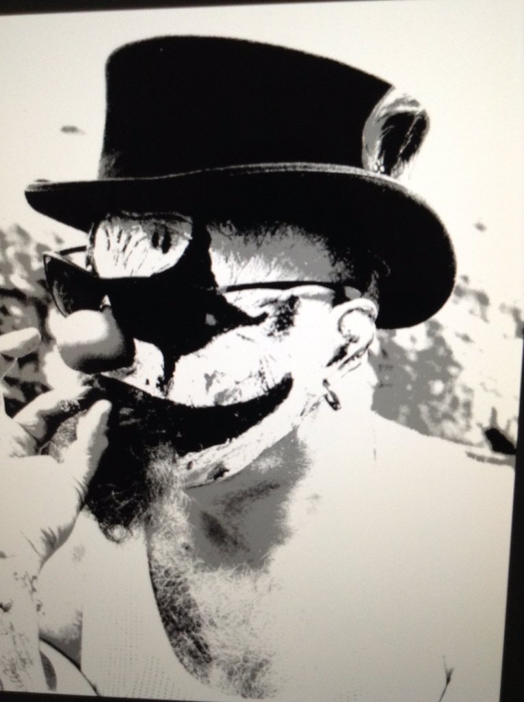 Black and white image of a clown smoking.