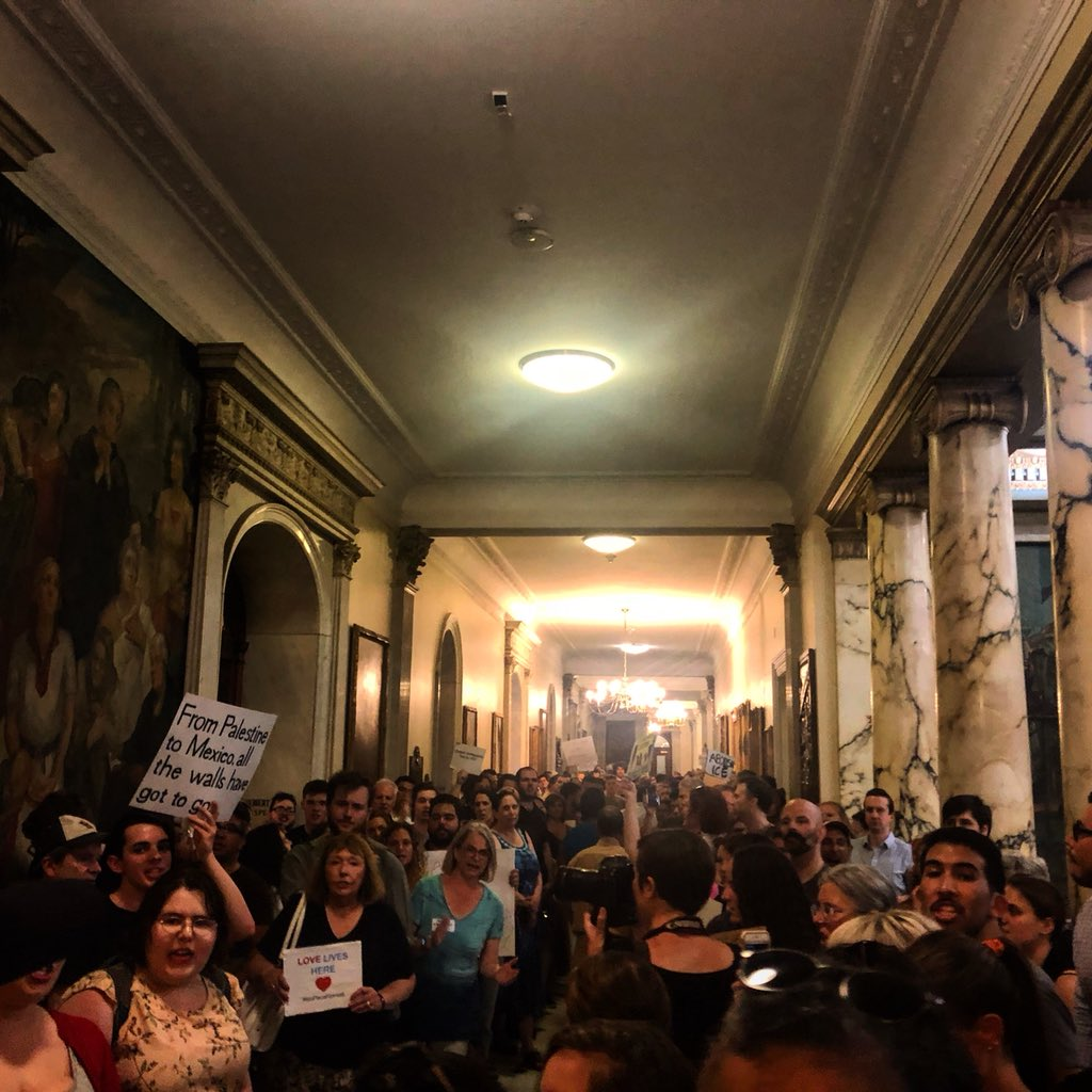 """The rally in support of immigrant families started outside the statehouse and is now inside near the west wing and the executive suite. Crowds are yelling, """"Gov. Baker, speaker of the house, we want you now!"""" A legislative aide of Gov. Charlie Baker said the governor isn't here."""