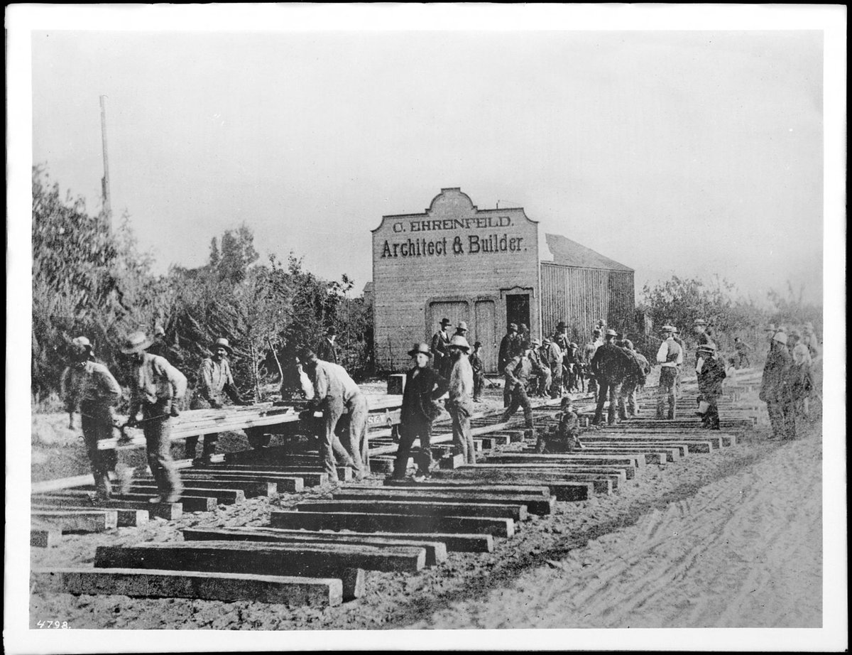 English: Photograph of work crews building the Los Angeles and San Gabriel Valley Railroad, South Pasadena, ca.1885. Dozens of men labor at the site, including a group about to lay a rail at left. A wooden building bears the sign &quot;C. Ehrenfeld, architect &amp; builder Datdecirca 1885 <br>http://pic.twitter.com/gbjs5QGCou