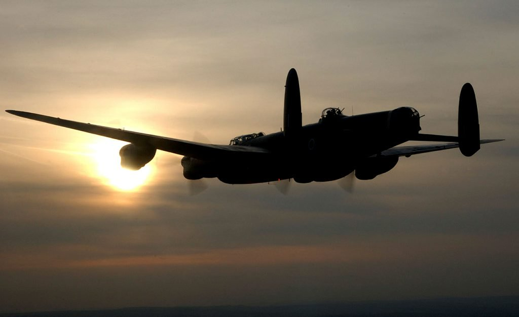 The Avro Lancaster with the Royal Air Forces Battle of Britain Memorial Flight based at RAF Coningsby, Lincolnshire is silhouetted against the setting sun.