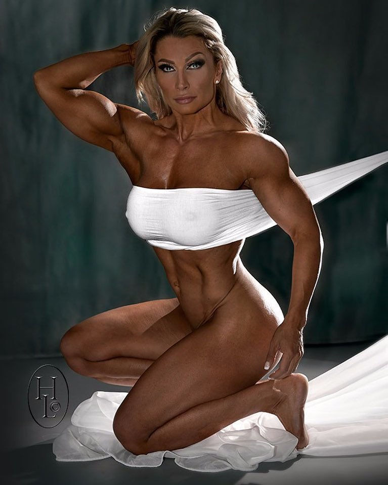 Mature Woman Standing Strong In The Gym And Flexing Muscles