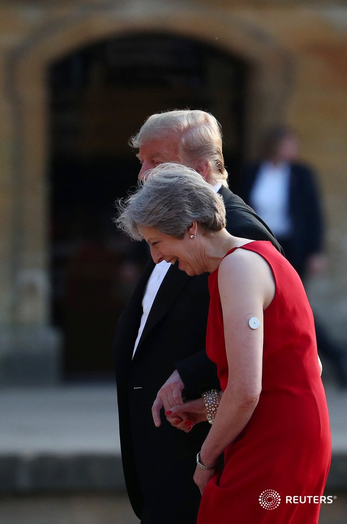 Theresa May and Donald Trump hold hands as they walk across the courtyard at Blenheim Palace, where they are attending a dinner