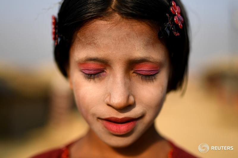 A Rohingya refugee girl named Amina poses for a photograph as she wears thanaka paste at Kutupalong camp in Cox's Bazaar, Bangladesh
