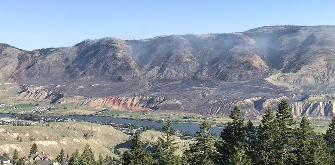 The hillside of the Shuswap Rd fire today - the kms of red retardant encircling the charred and smoldering landscape looks like a child's magic marker outline! #Kamloops #BCWildfire Photo