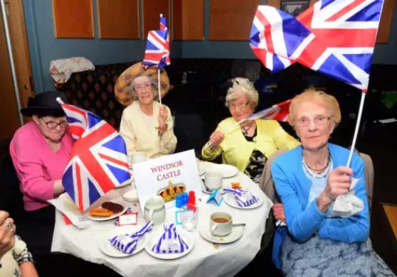 Old ladies with union flags having afternoon tea