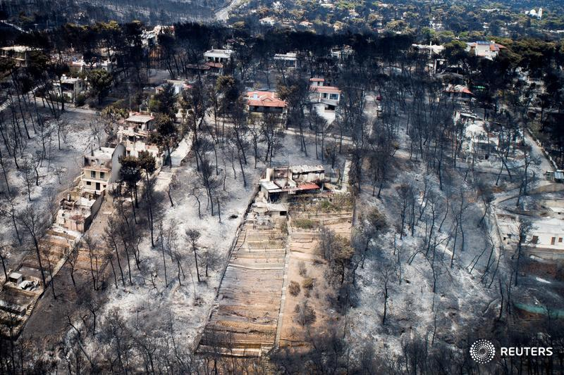 An aerial view of burnt houses and trees in the village of Mati