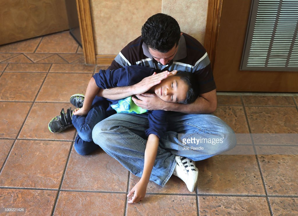 EL PASO, TX - JULY 25: A man, identified only as Renan, spends time with his son, Nathan,11, as they are cared for in an Annunciation House facility after they were reunited with each other on July 25, 2018 in El Paso, Texas.